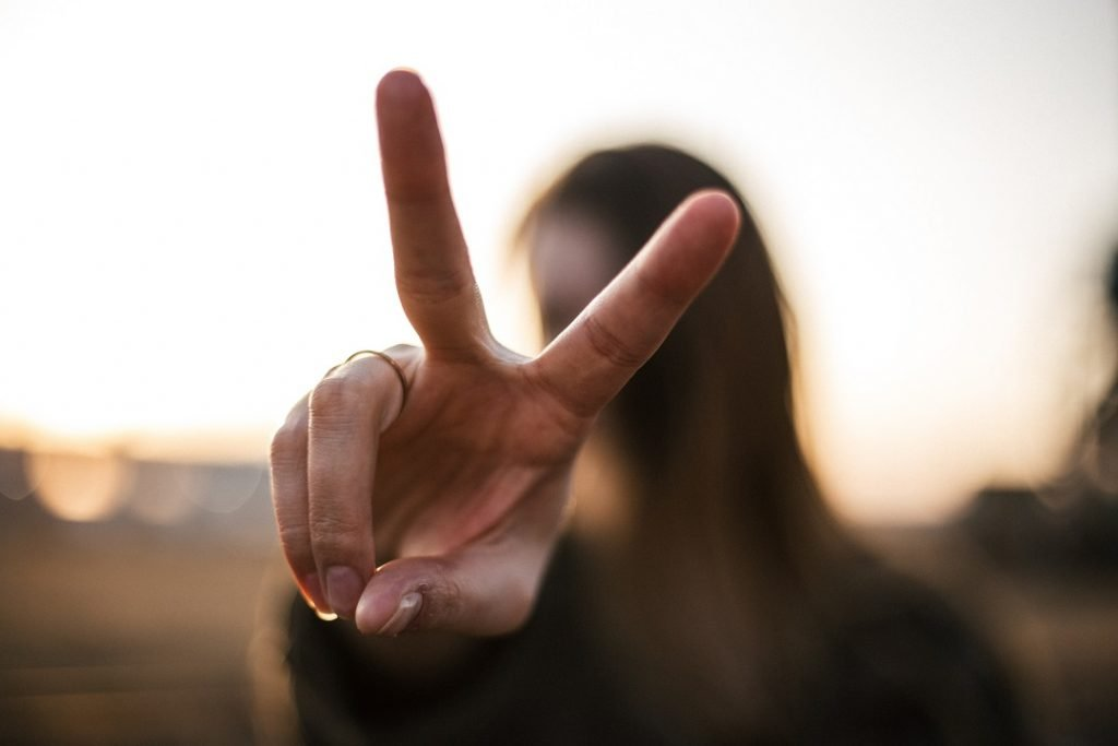 "Girl holding up two fingers - signifying two things to remember with the pronunciation of ""itis""."